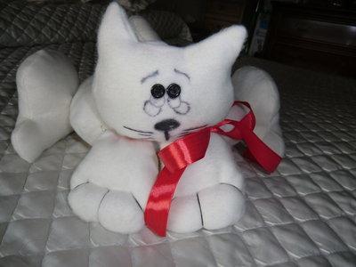 Pupazzo gatto in panno imbottito color bianco con fiocchi rossi. Ideale per abbellire i letti dei bambini