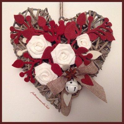 Cuore di vimini con rose di lino bianche e rametti di feltro rossi