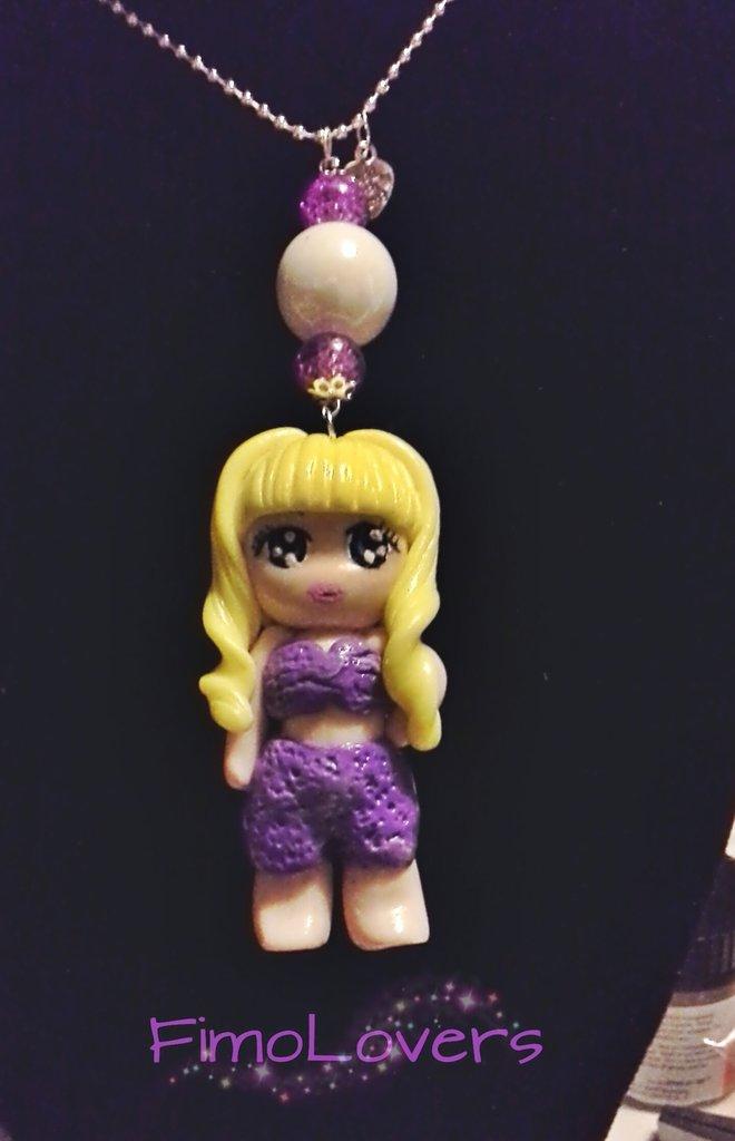 Collana, realizzata a mano, in fimo, con bambola in tenuta estiva, sui toni del violetto.