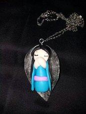 Collana, realizzata a mano, in fimo, con giapponesina kokeshi,  distesa su una foglia..