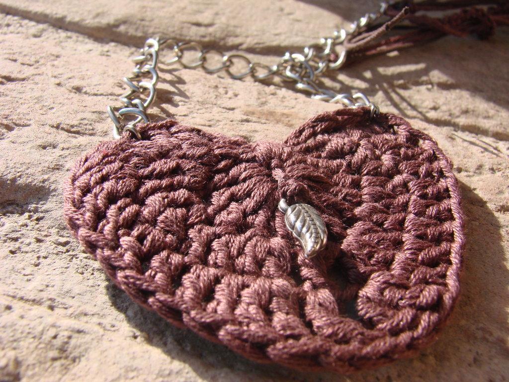 Collana con catena in metallo, cordincino e filo di cotone. Ciondolo in cotone a forma di cuore lavorato all'uncinetto.