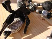 Collana con perline fatte a mano con carta di quotidiani e con fili di lana intrecciati intervallate da perline in plastica nere e grigie.