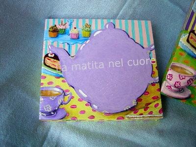 Lavagna piccola teiera lilla con tazza di the fumante cupcakes e torta