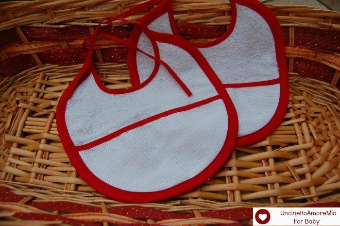 Bavaglini  bimbi con  bordo rosso: in  cotone e spugna ricamati a mano punto croce