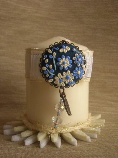 Candela decorata con ciondolo di metallo rotondo e perline realizzato in pasta polimerica
