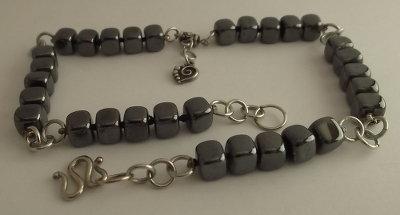 Collana di perle di vetro color ematite con cuore pendente argentato