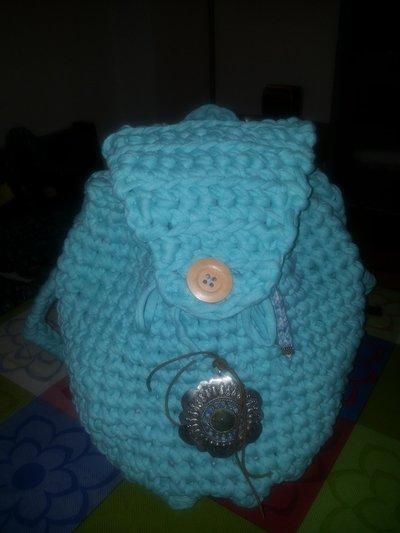 zainetto azzurro in fettuccia con decorazione etnica in metallo e pietre