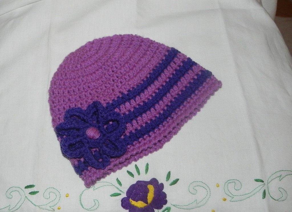 Cappellino bambina con fiore fatto a mano ad uncinetto toni del viola con fiore