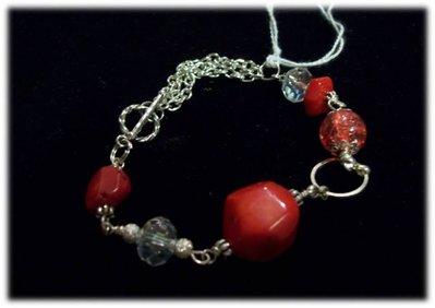 Bracciale con pietre rosse e catena argentata.