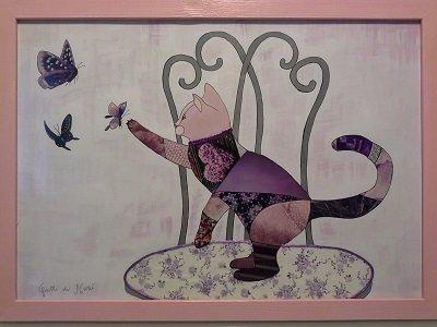 Quadro con gatto su sedia che gioca con farfalle