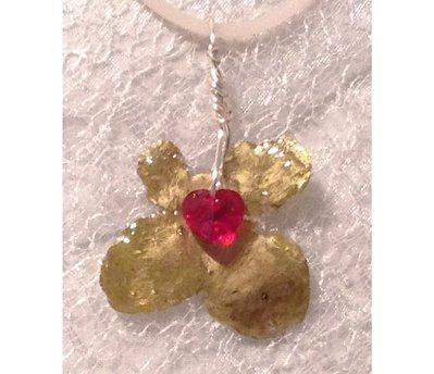 Ciondolo di quadrifoglio dorato con cuore rosso di cristallo swarovski.