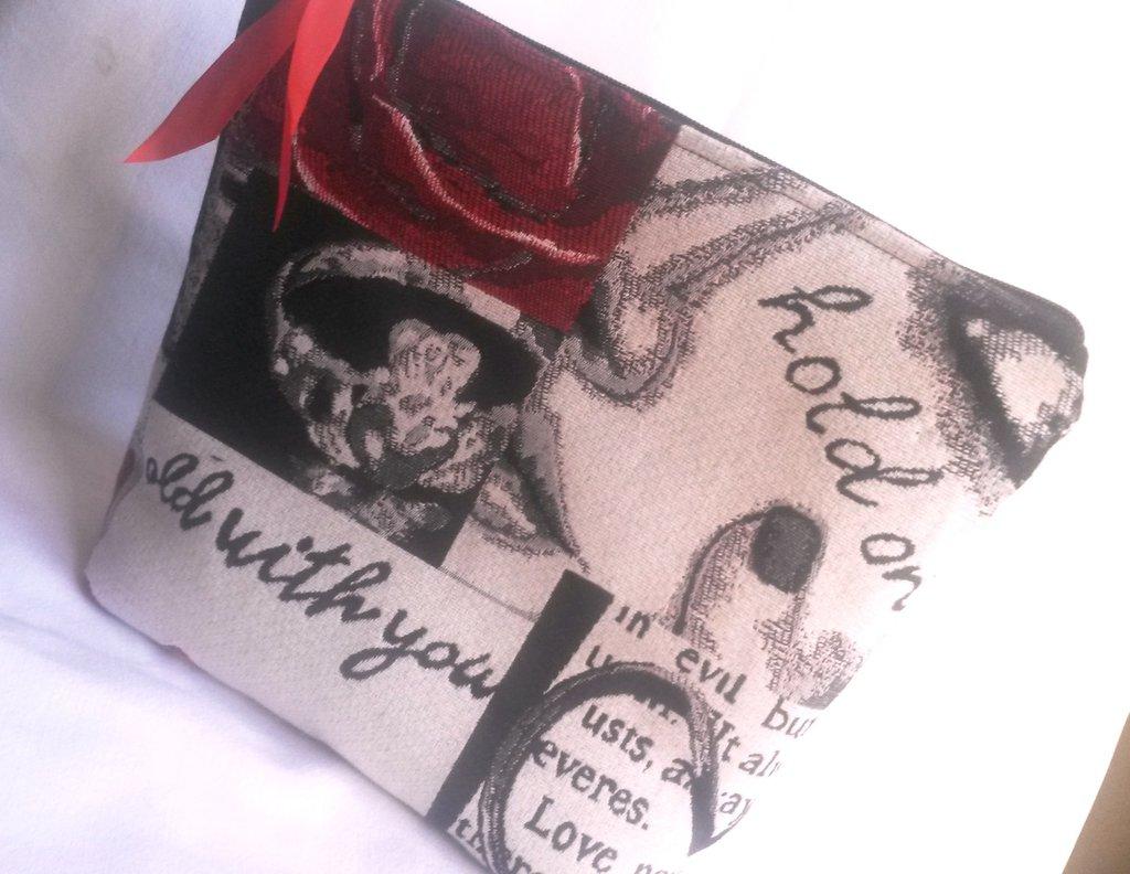 pochette in stoffa bianca con disegni grigi neri e rossi