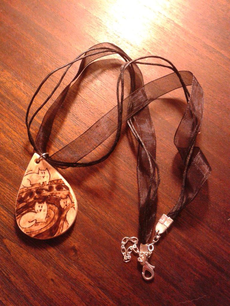 collana decorata con gatti pirografati.