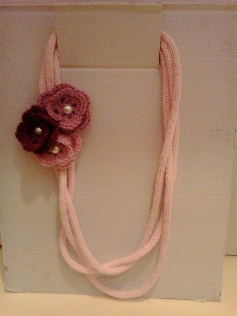 Collana in lana rosa lavorata a tricotin con tre fiori
