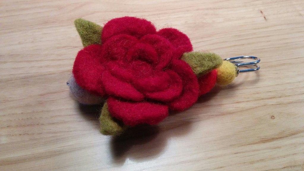 Spilla a forma di rosa in lana cotta