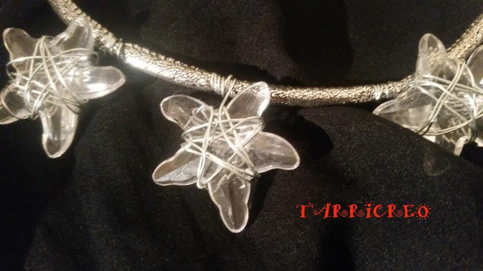 Collana ASTREA . Collana realizzata con fettuccia rigida color argento , con inserzioni di pietre trasparenti a forma di stella, con lavorazione in filo di metallo morbido.