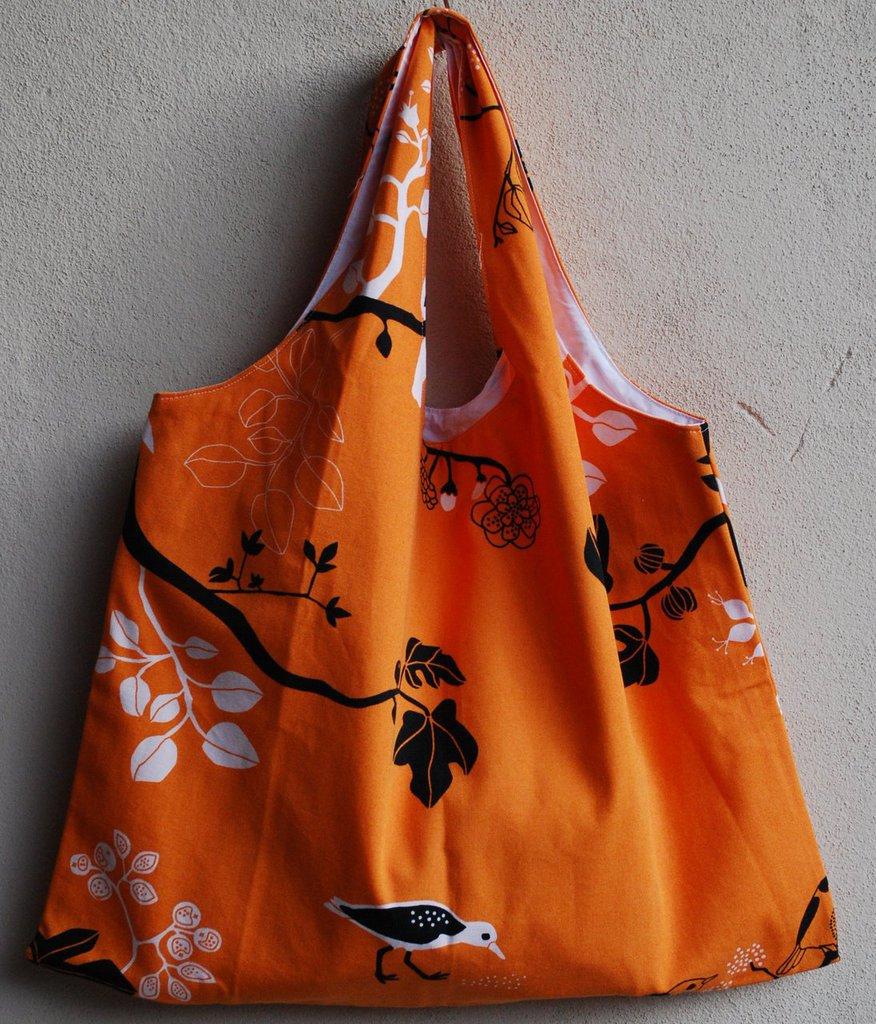 Borsa reversibile arancione con motivo a rami e passerotti