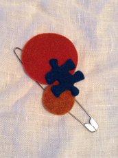 Spillone in metallo con figure geometriche e puzzle in lana cotta