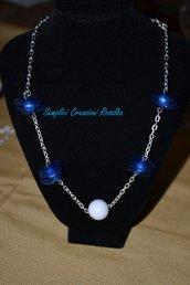 collana con decori realizzati con pepite di plastica blu e perle bianche, con perla bianca centrale