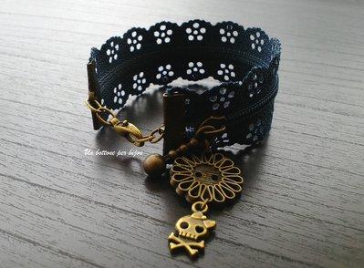 Bracciale cerniera effetto pizzo con bottone d'epoca in bronzo a forma di fiore e ciondolo teschio
