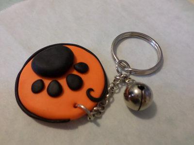 Portachiavi zampina arancione/nero campanellino e perline