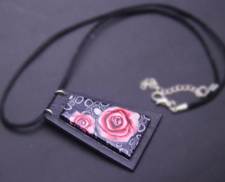 Necklace with red roses fancy  on trapezoidal pendant.