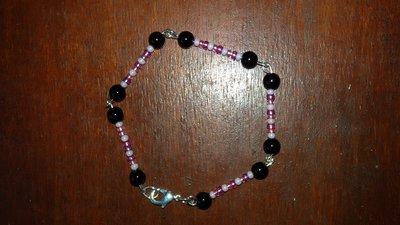 Bracciale con perline rosa e nere e chiusura a moschettone