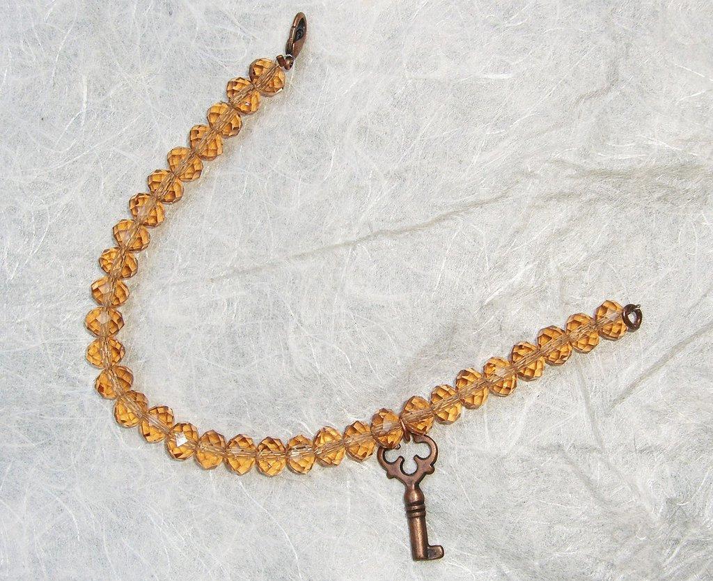 Bracciale in cristallo marrone e charm di rame a forma di chiave