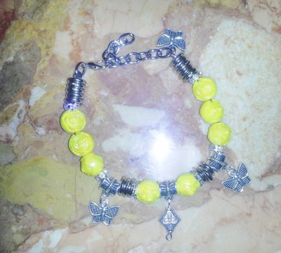 bracciale con perle iridescenti gialle intagliate a fiore e charms