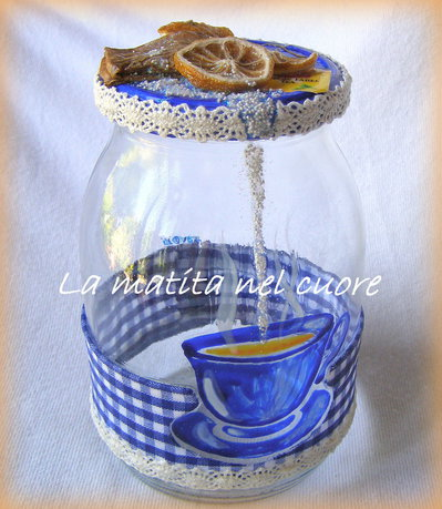 Barattolo di vetro con tazza blu dipinta, tovaglia, the, limone e zucchero