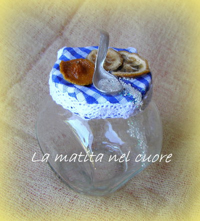 Zuccheriera di vetro con limone vero, cucchiaino fatto a mano, zucchero e tovaglia vichy