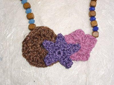 Collana in legno e filati vari lavorati a uncinetto sui toni del viola e del rosa