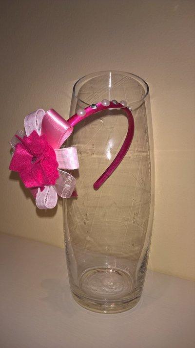 Cerchietto per capelli fucsia decorato con fiore di feltro, nastri e strass.