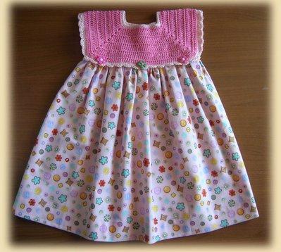 Vestitino con corpino realizzato all'uncinetto in filo rosa e gonnellina in cotone stampato con deliziosi bottoncini