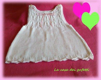 Vestitino in filo bianco con nastrino rosa realizzato ai ferri per bimba