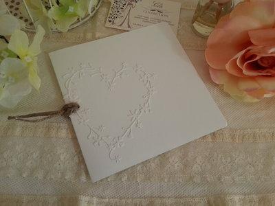 Partecipazione di nozze con cuore applicato in cartoncino rigato e fiocco di juta