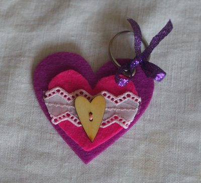 Portachiavi in feltro VIOLA a forma di CUORE.Decorato con feltro fuchsia,pizzo sangallo bianco-rosa e bottone-cuore- in legno.Nastrino lamè