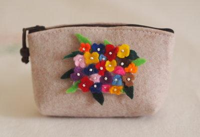 Pochette portatrucco in feltro.Decorata con medaglione di fiori in feltro e perline.Perla in legno appesa alla cerniera.Fatta a mano.