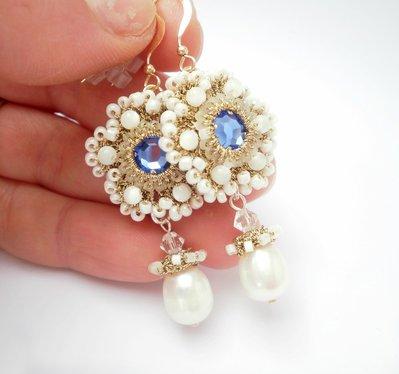 orecchini dorati ricamati con le perle di madreperla, arricchiti con strass azzurro