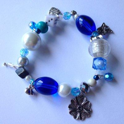 Braccialetto elastico Sfumature d'azzurro, con perline multiformi e ciondolini a fiore, fatto a mano