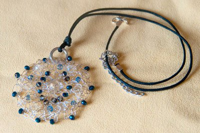Ciondolo in filo di metallo color argento lavorato all'uncinetto con perle di vetro blu