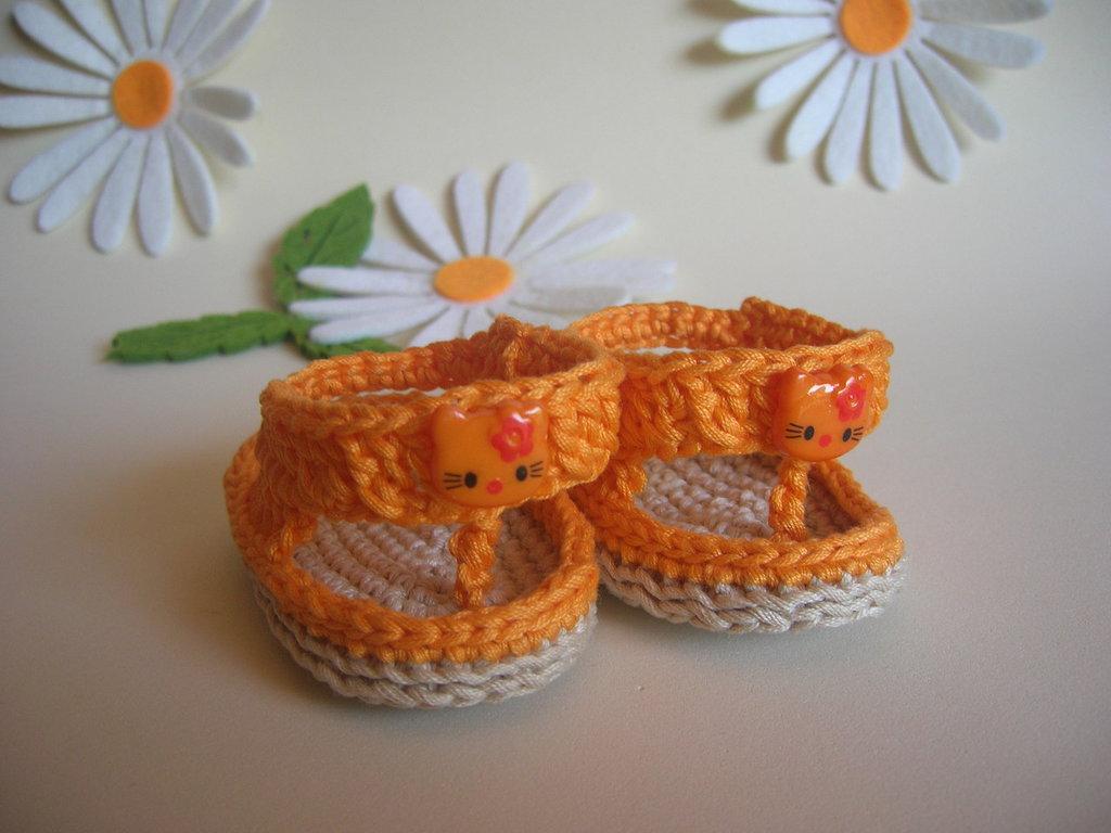 Scarpine per neonato in filo arancione con bottoncino a forma di gattino
