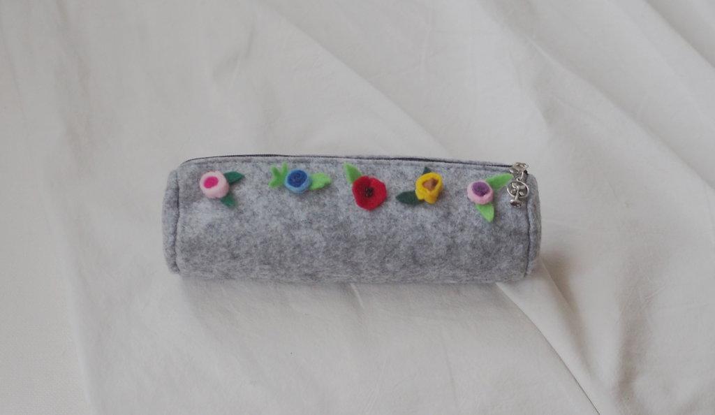 Astuccio in feltro grigio, con applicazione di piccoli fiori in feltro e perline e ciondolo in metallo sulla cerniera.Porta trucco,penne,piccoli oggetti.Fatto a mano