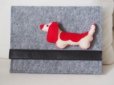 Porta tablet (o notes ,cellulare e penne) in feltro.Applicata una spilla in feltro,un cane bianco e rosso ricamato a mano,imbottito.Chiusura in velcro