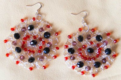 Orecchini in filo di metallo color argento lavorato all'uncinetto con perle di vetro nere e rosse