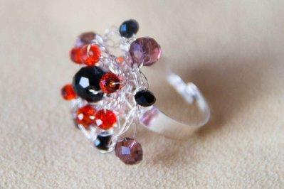 Anello  in filo di metallo color argento lavorato all'uncinetto con perle di vetro nere e rosse