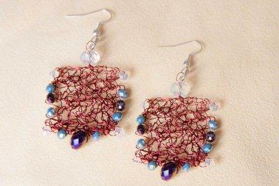 Orecchini in filo di alluminio rosso lavorato all'uncinetto con perle di vetro colorate