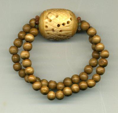 Bracciale elastico in legno chiaro con centrale in osso traforato e istoriato