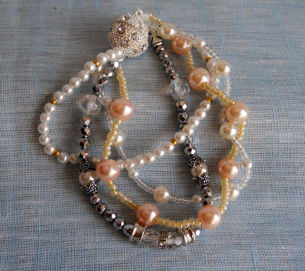 Elegante braccialetto a quattro fili con perle bianche, perle rosate,pietre dure, elementi Svarowski. Chiusura magnetica.