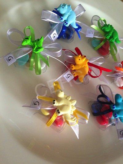 Bomboniera a borsetta in plastica trasparente decorata con dinosauri colorati realizzati in pasta FIMO